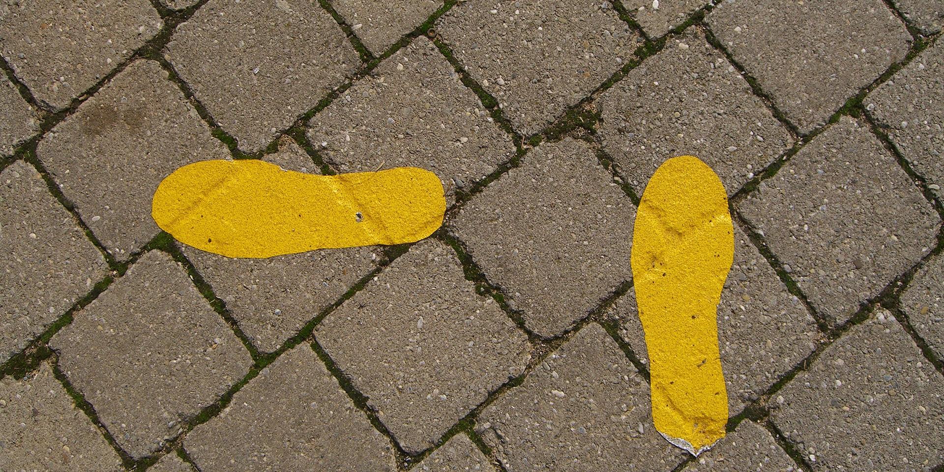 Gelbe Fußspuren auf Asphalt