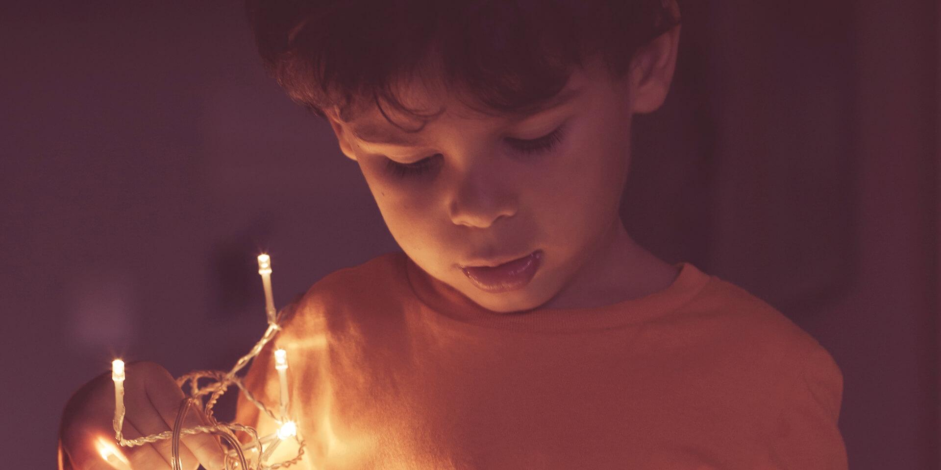 Kleiner Junge mit Lichterkette in der Hand