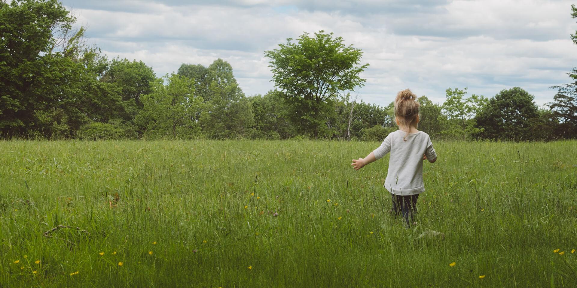 Mädchen läuft über eine Wiese