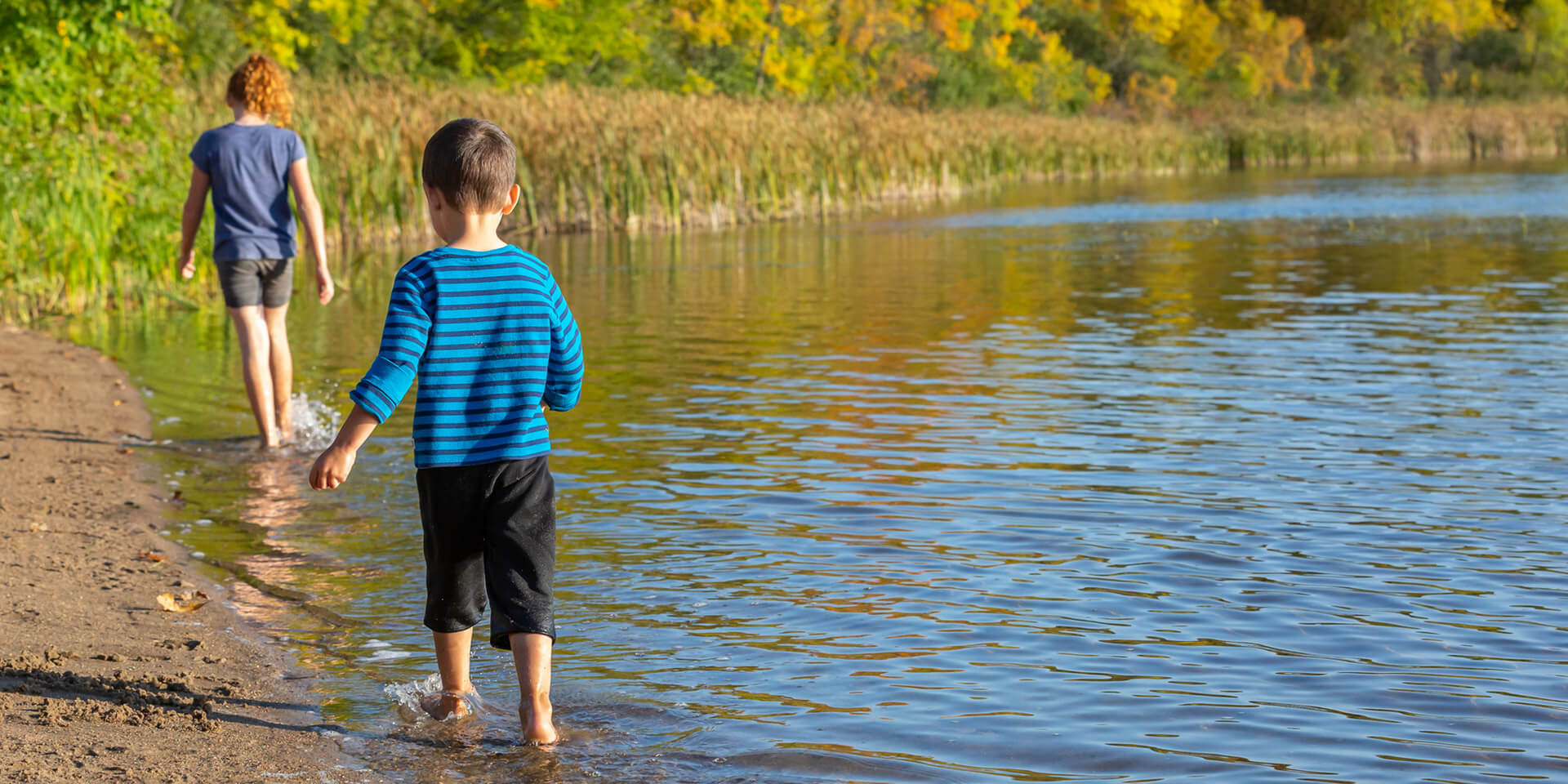 Kinder gehen am Ufer entlang