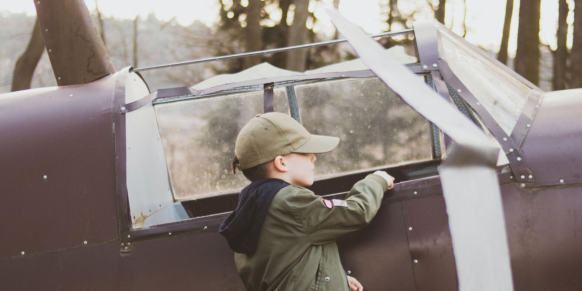 Junge untersucht ein altes Flugzeug
